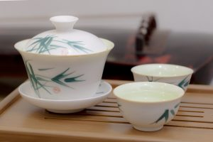 Tea cup with guqin as background